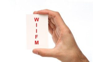 hand holding a card with WIIFM on it